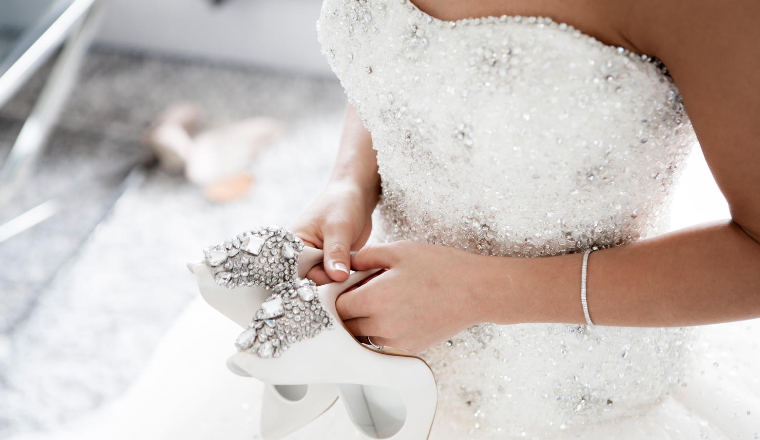 Woman in white wedding gown holding white heels